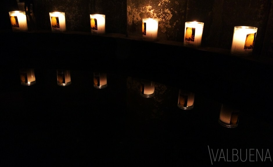 Votive candles next to a baptismal font