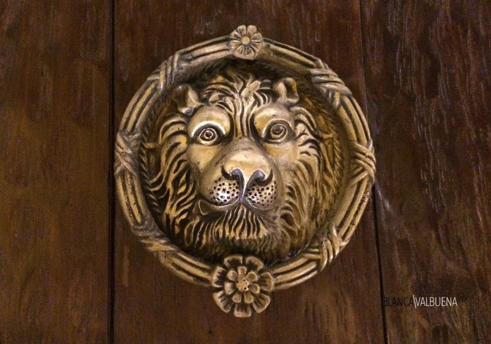 A lion door knob that has flowers as decor