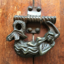 A mermaid seems to nap on one of Cartagena's door knockers